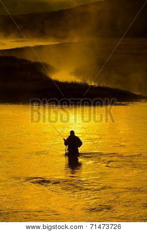 Man fishing in river with fly rod and waders