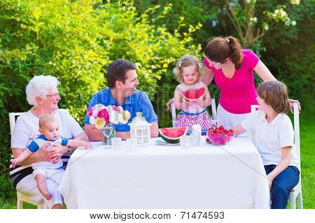 Family Eating Fruit In The Garden