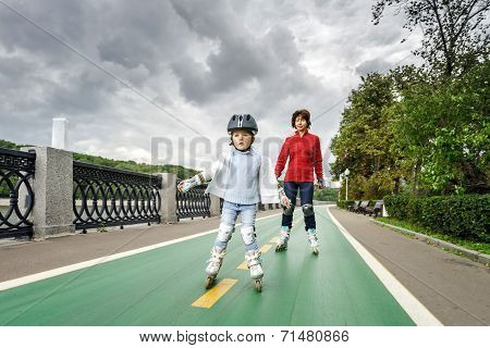 Cute Little Girl Learning Rollerskating With Her Mother