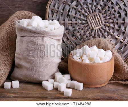 Refined sugar in bag and bowl on wooden background