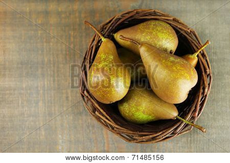 Ripe pears in wicker basket, on wooden background