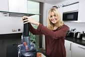 picture of juicer  - Portrait of young blond woman using juicer for juicing carrots in kitchen - JPG