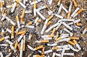 stock photo of discard  - Cigarette butts discarded in ashtray of sand background