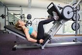 stock photo of leggings  - Side view of a fit young woman doing leg presses in the gym - JPG