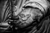 pic of priceless  - Dirty hands of a beggar with some coins - JPG