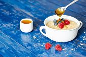 picture of porridge  - Porridge with berries and honey  on a blue wooden table - JPG