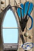 picture of spearfishing  - Small wooden row boat with empty blue paper inside on wooden wall with equipment for spearfishing seashells and starfish - JPG