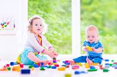 picture of little sister  - Adorable laughing toddler girl and a funny little baby boy brother and sister playing with colorful blocks sitting on a floor in a sunny bedroom with a big window - JPG