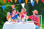 stock photo of holland flag  - Happy big Dutch family with kids celebrating a national holiday or sport victory having fun at a grill party in a garden decorated with flags of Netherlands screaming Hup Holland - JPG
