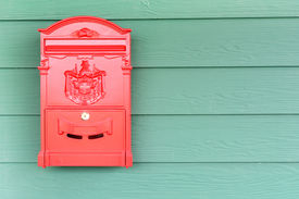 pic of mailbox  - a red mailbox with green wood background - JPG