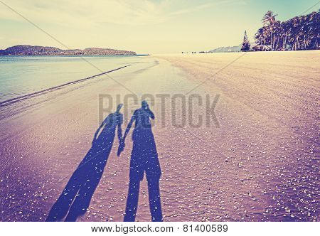 Vintage Retro Filtered Picture Of Couple's Shadow On Beach.