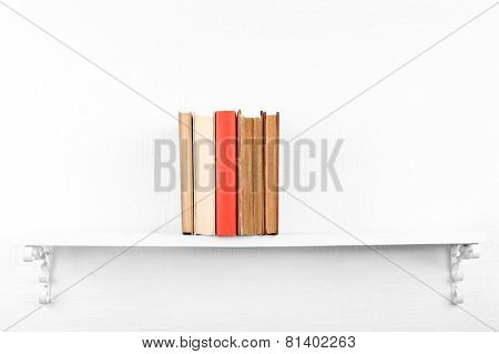 Old books on bookshelf on white wall background