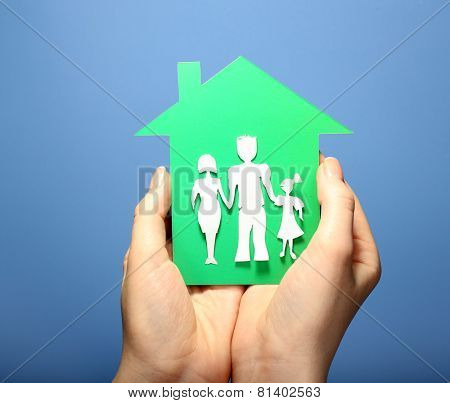 Cutout house with paper family in female hands on colorful background