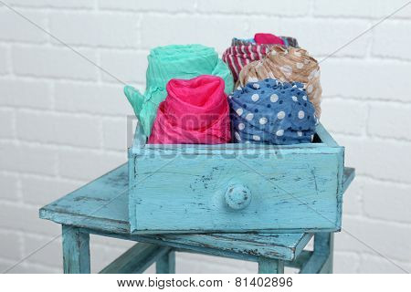 Different scarves in color drawer on white brick wall background