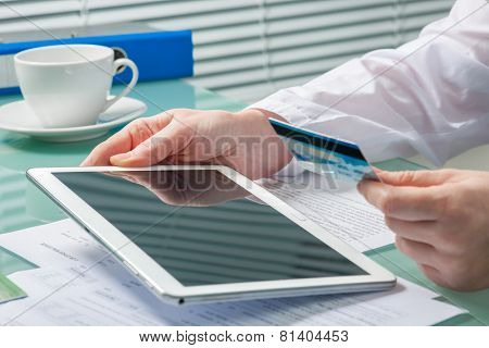 Woman using a credit card and digital tablet for buying on-line