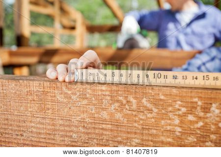 Closeup of architect's hand measuring wood at construction site