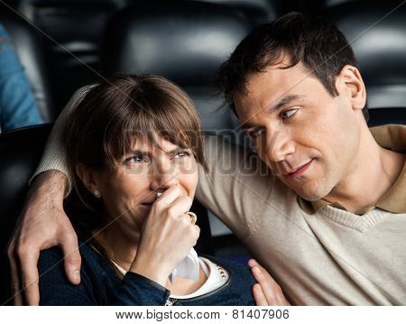 Mid adult man looking at woman crying while watching movie in cinema theater