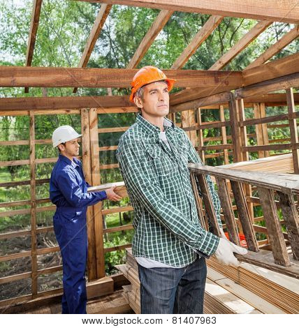 Male construction workers carrying ladder and wooden planks in timber cabin at site