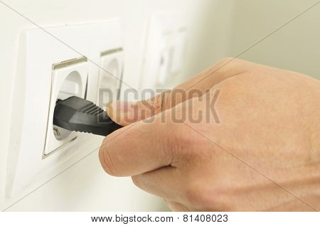 closeup of the hand of a man plugging in or unplugging an electrical plug in a socket