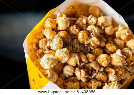 Closeup of roasted popcorns filled in paperbag at cinema theater