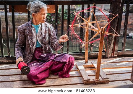 INLE LAKE, MYANMAR - JANUARY 8, 2014: Burmese woman wheel spinning yarn at weaving factory where textile is manufactured in traditional way