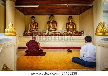 YANGON, MYANMAR - JANUARY 3, 2014: Man and Buddhist mokn meditating and worshipping statues of Buddha in Shwedagon Paya pagoda
