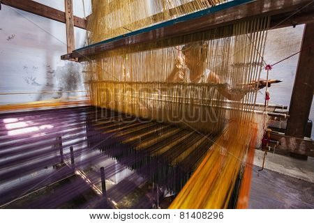 KANCHIPURAM, INDIA - SEPTEMBER 12, 2009: Man weaving silk sari on loom. Kanchipuram is famous for hand woven silk sarees and most of the city's workforce is involved in  weaving industry