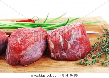fresh fillet chops : raw beef fillet on wooden board with thyme and red hot dry pepper ready to prepare . isolated over white background