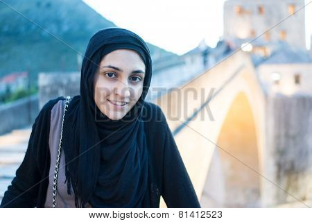 Arabic Muslim Middle Eastern girl traveling for vacation in Mostar bridge