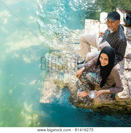 Muslim family taking ablution in river of Buna
