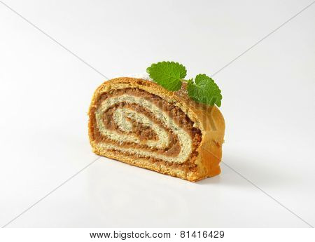 single slices of nut roll dusted with sugar and decorated with leaf of mint