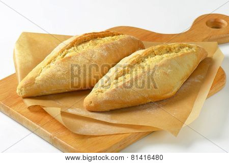 two fresh crunchy baguettes on the wooden board