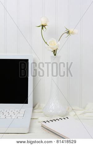 Closeup of a white wood desk with a white laptop and milky vase with white roses. A spiral bound pad an some flower petals are next to the laptop. Vertical format with a beadboard background.