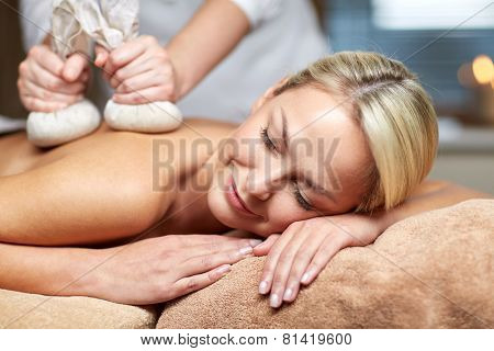 people, beauty, spa, healthy lifestyle and relaxation concept - close up of beautiful young woman lying and having herbal bag massage in spa