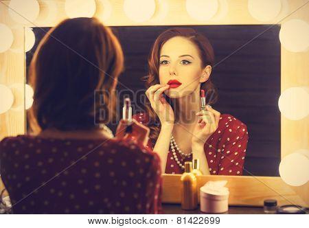 Portrait Of A Beautiful Woman As Applying Makeup Near A Mirror