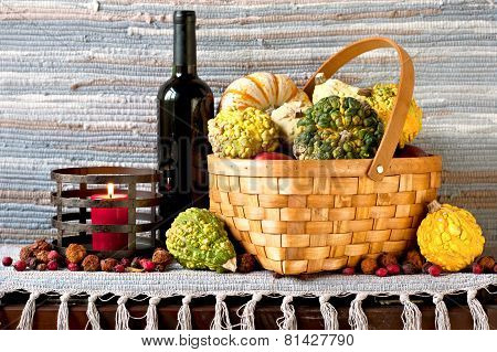 Many Pumpkins In Wicker Basket With Bottle Of Red Wine.