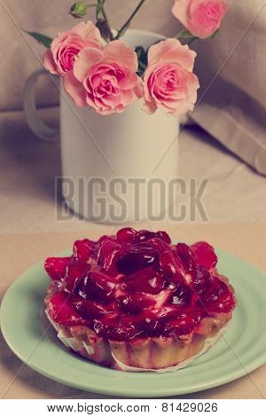 Strawberry tart and bouquet of roses