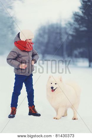 Winter And People Concept - Boy With White Samoyed Dog Outdoors In Winter Day