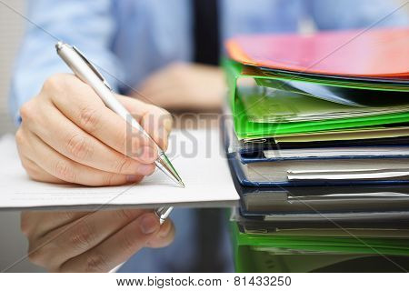 Businessman Is Writing On Document And A Lot Of Documentation Is Waiting To Be Reviewed