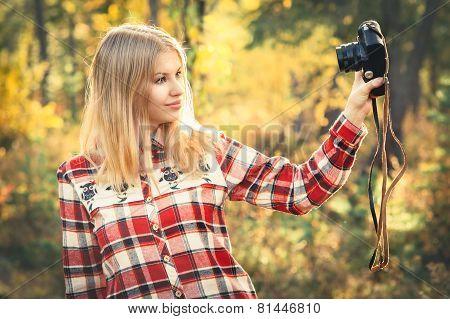 Young Woman wearing plaid shirt with retro photo camera taking selfie shot outdoor