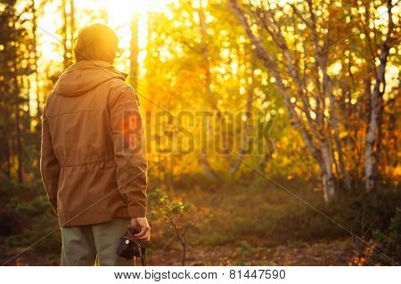 Young Man with retro photo camera outdoor Travel Lifestyle sunset forest nature on background