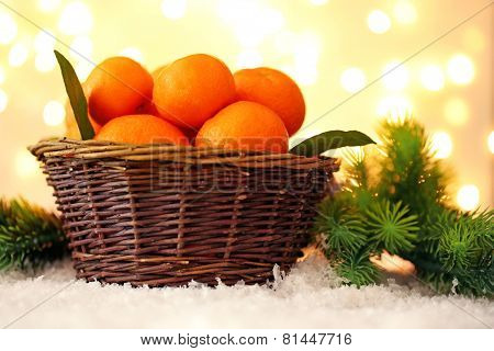Fresh ripe mandarins in wicker basket, on snow, on lights background