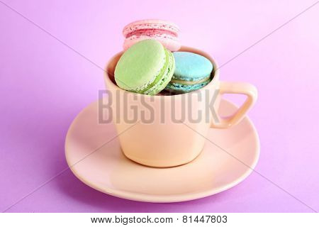 Assortment of gentle colorful macaroons in colorful mug on color background