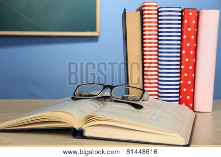 Textbooks with glasses on wooden desk, on colorful wall and blackboard background
