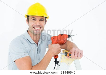 Portrait of happy technician holding drill machine while leaning on step ladder