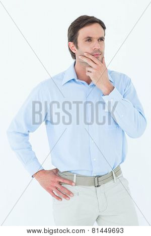 Thoughtful businessman with hand on chin looking away over white background