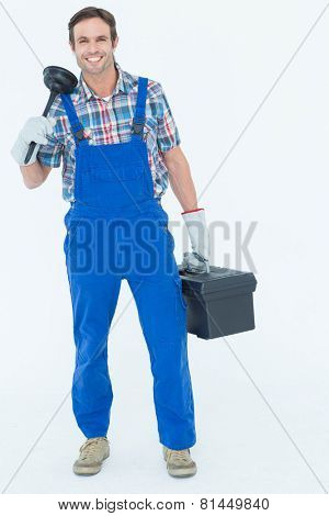 Full length portrait of plumber holding plunger and tool box over white background