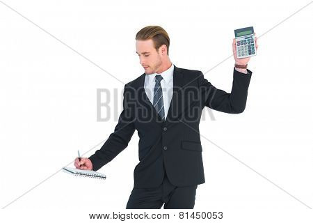 Serious businessman holding calculator taking notes on white background
