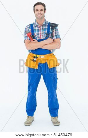 Full length portrait of confident plumber holding monkey wrench and plunger over white background