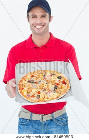 Portrait of happy delivery man showing fresh pizza on white background